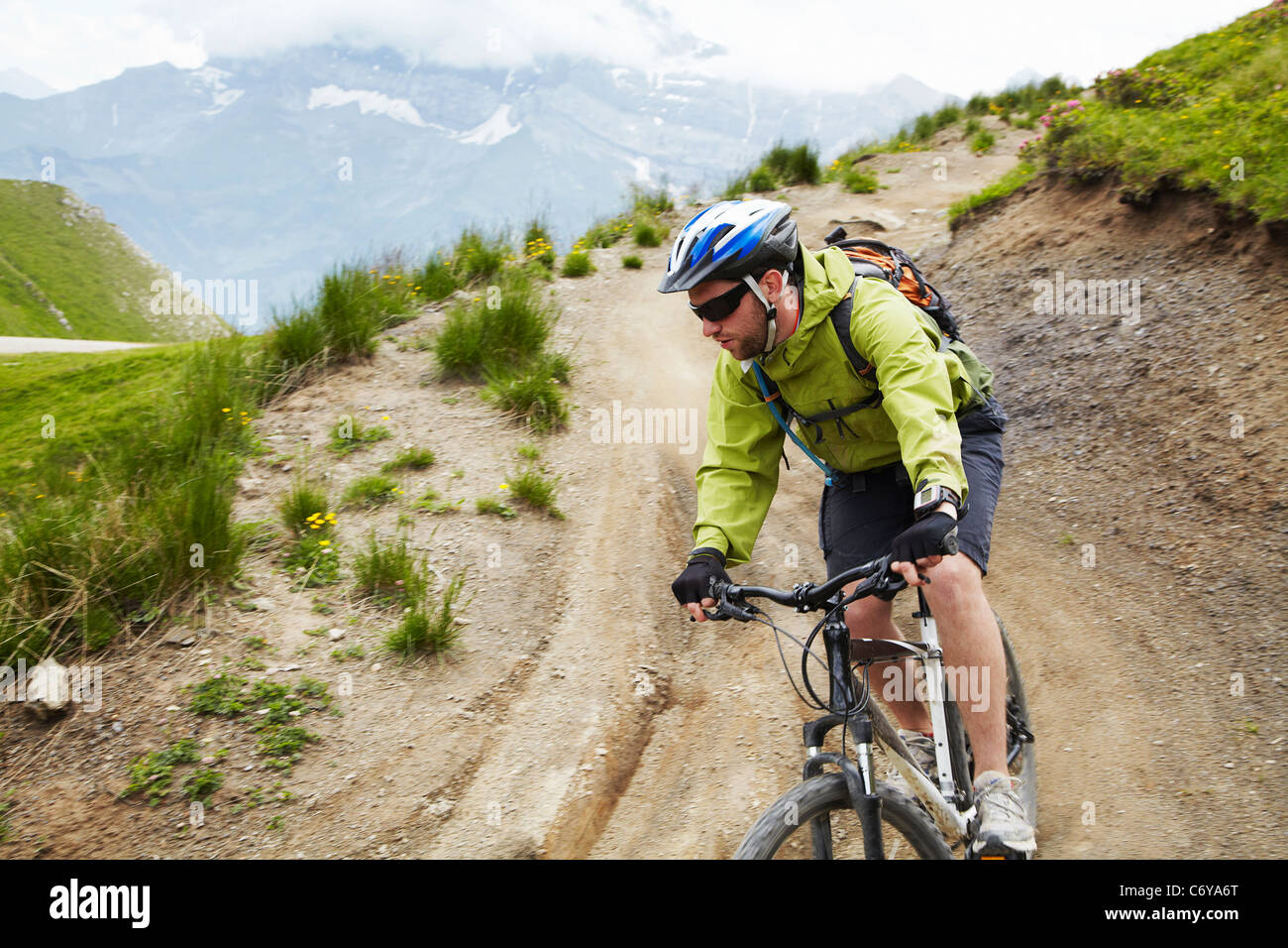 Mountain biker on dirt road - Stock Image