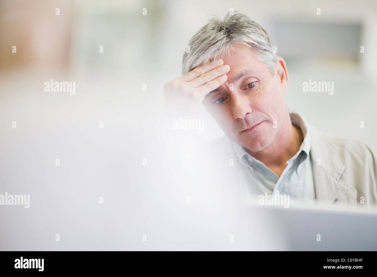 Stressed businessman working in office - Stock Image