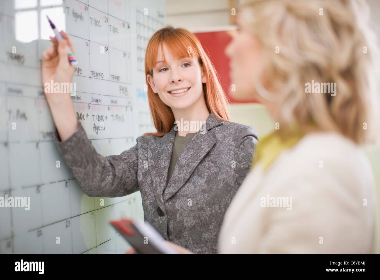 Businesswomen writing on calendar - Stock Image