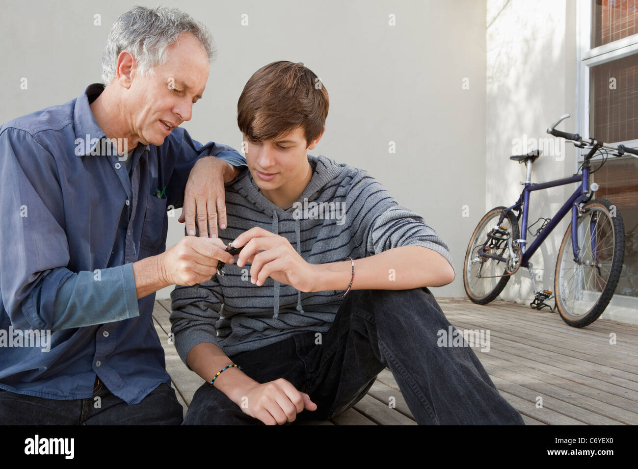 Father and son examining tool together - Stock Image