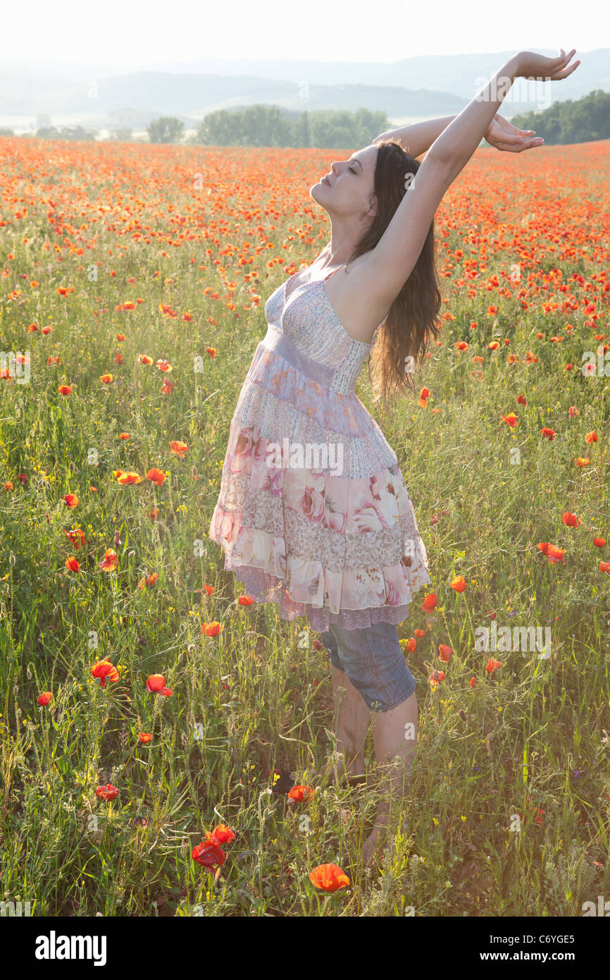 Pregnant woman in field of flowers - Stock Image