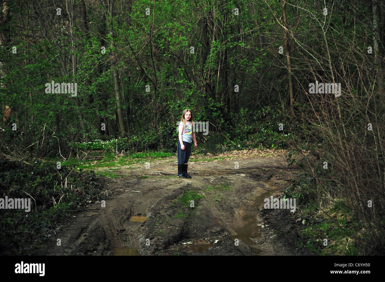 Girl walking on dirt road in forest - Stock Image