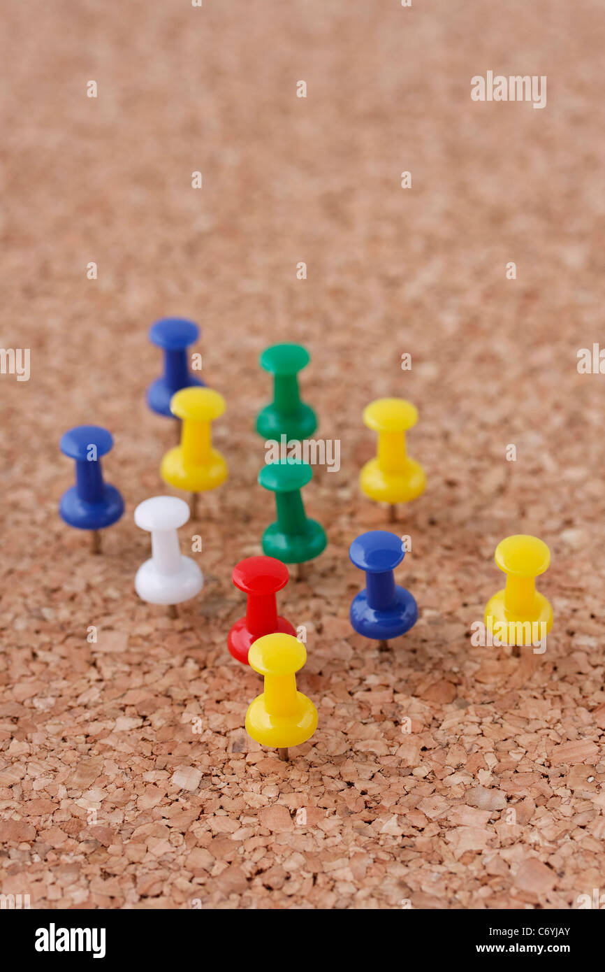 arrangement of pushpins pinned on cork board - Stock Image