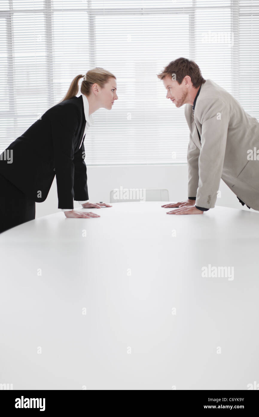 Rival business people leaning over desk - Stock Image