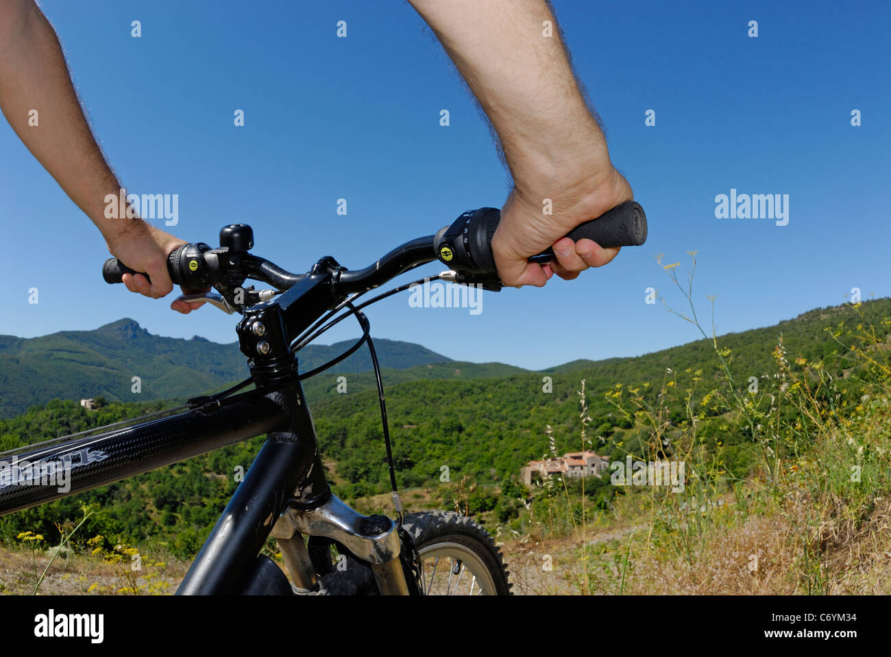 Cyclist cycling and mountain biking in the hills on a mountain bike, Cevennes, France - point of view - Stock Image