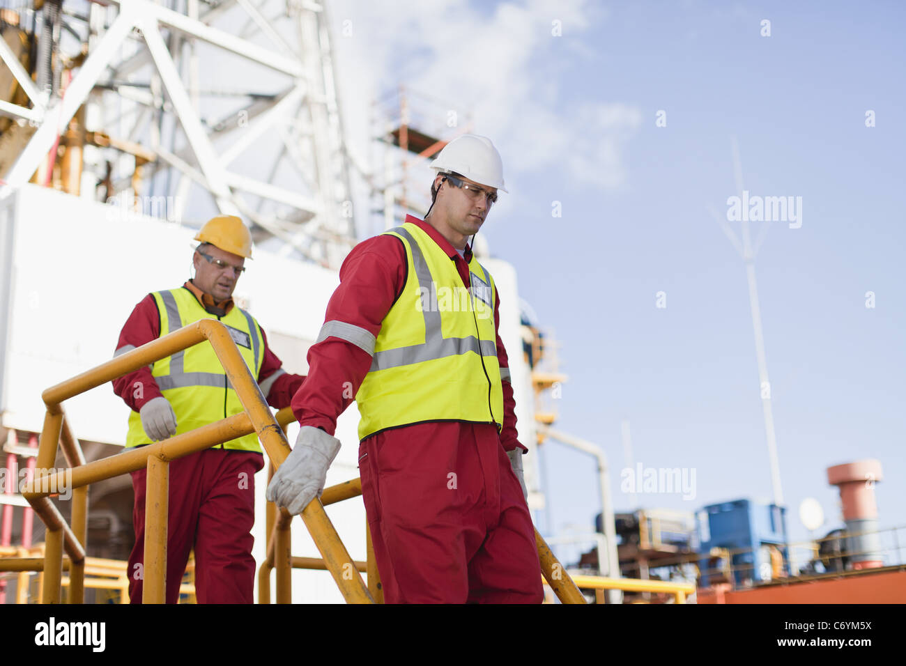 Workers walking on oil rig - Stock Image