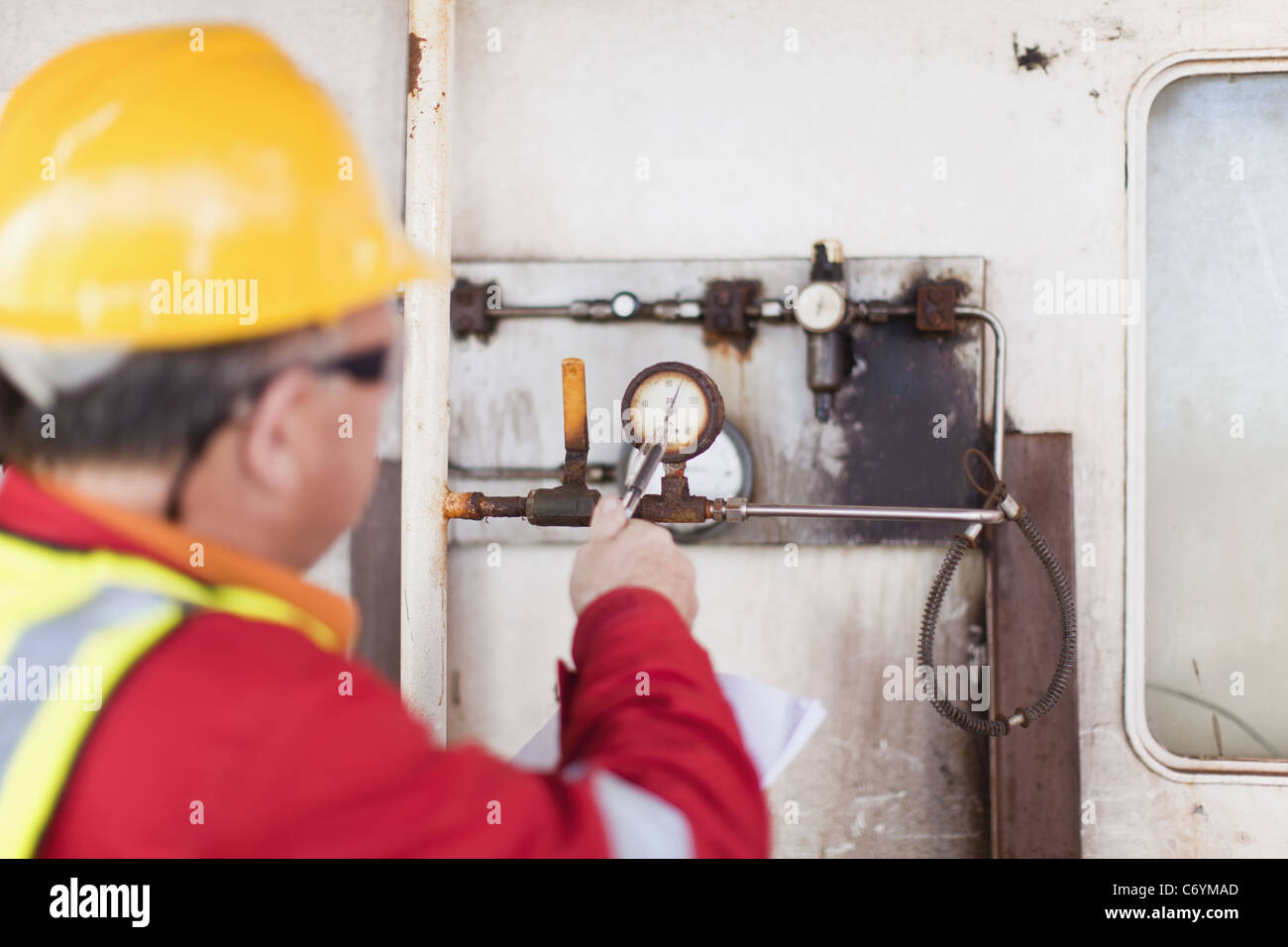 Worker checking gauge on oil rig - Stock Image