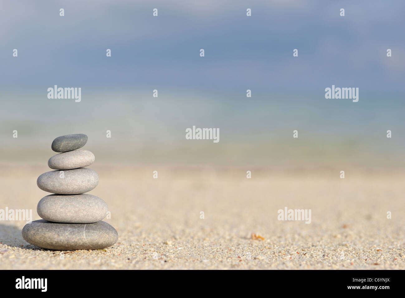 Stack of pebbles on beach, by a tropical sea - Stock Image
