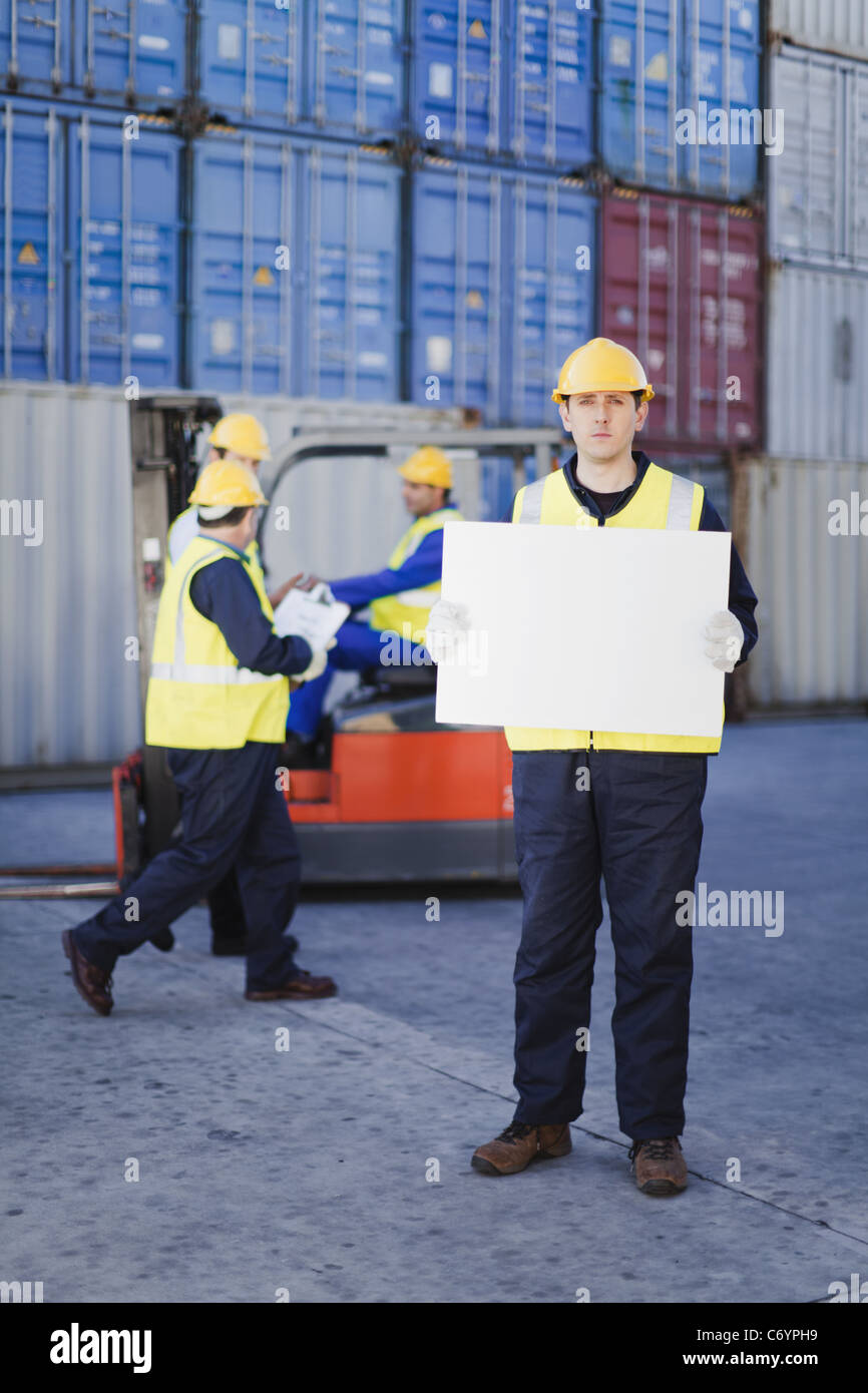 Worker holding sheet in shipping yard - Stock Image