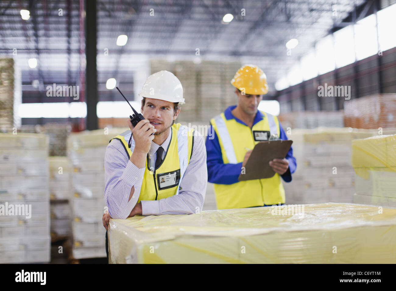 Worker using walkie talkie in warehouse - Stock Image