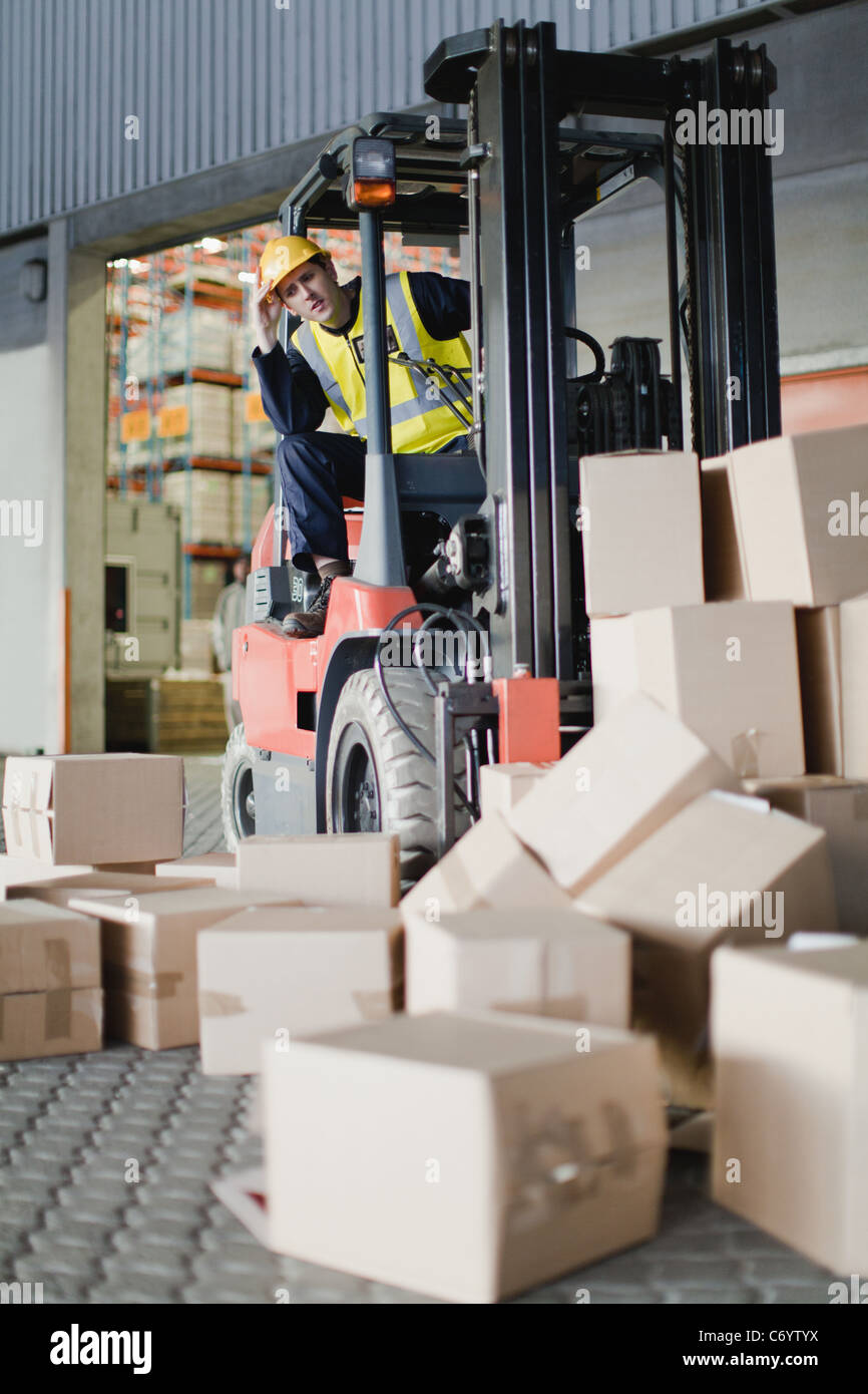 Worker using forklift to pick up boxes - Stock Image