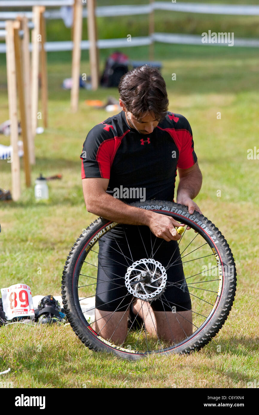 Male mountain bike racer repairs flat tire during off-road triathlon race event - Stock Image