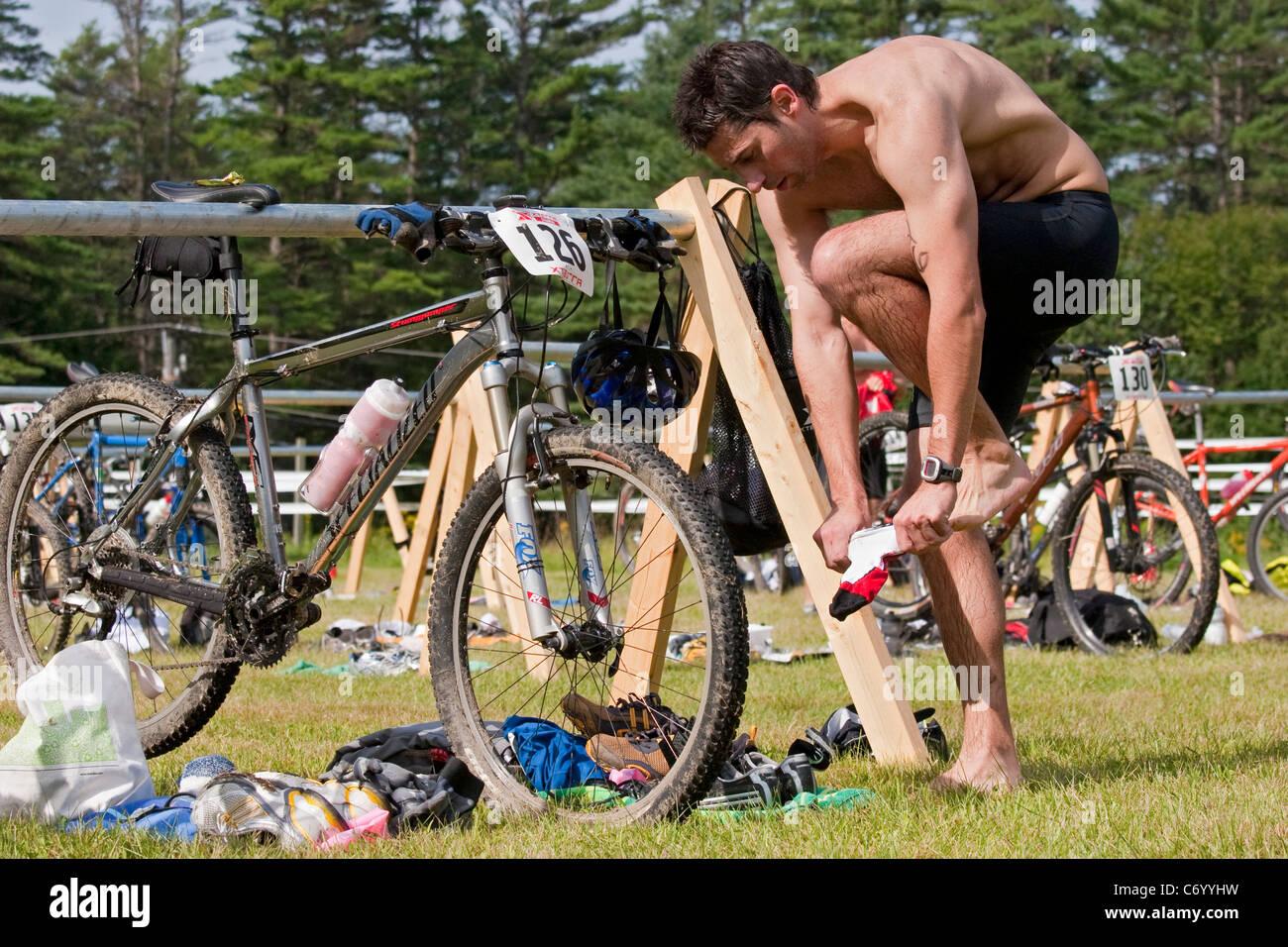 Male triathlon racer changes equipment during off-road triathlon race event before mountain biking - Stock Image