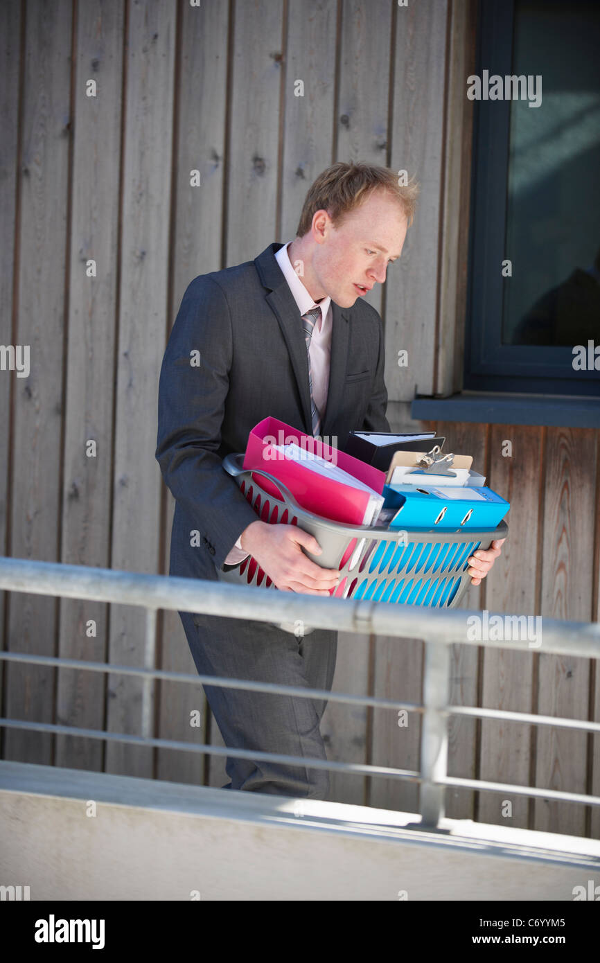 Businessman carrying box of supplies - Stock Image