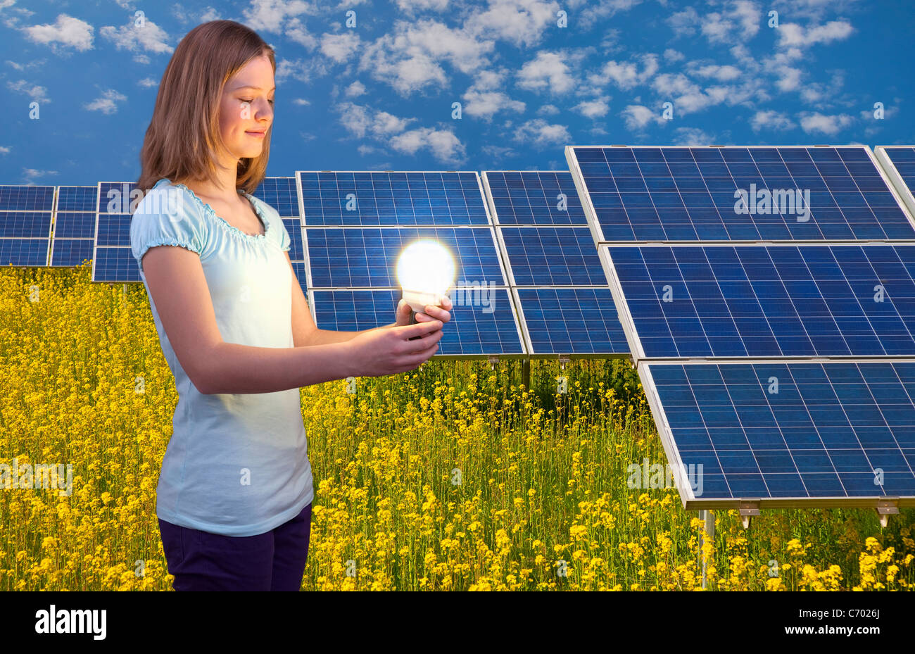 Woman with lightbulb and solar panels - Stock Image