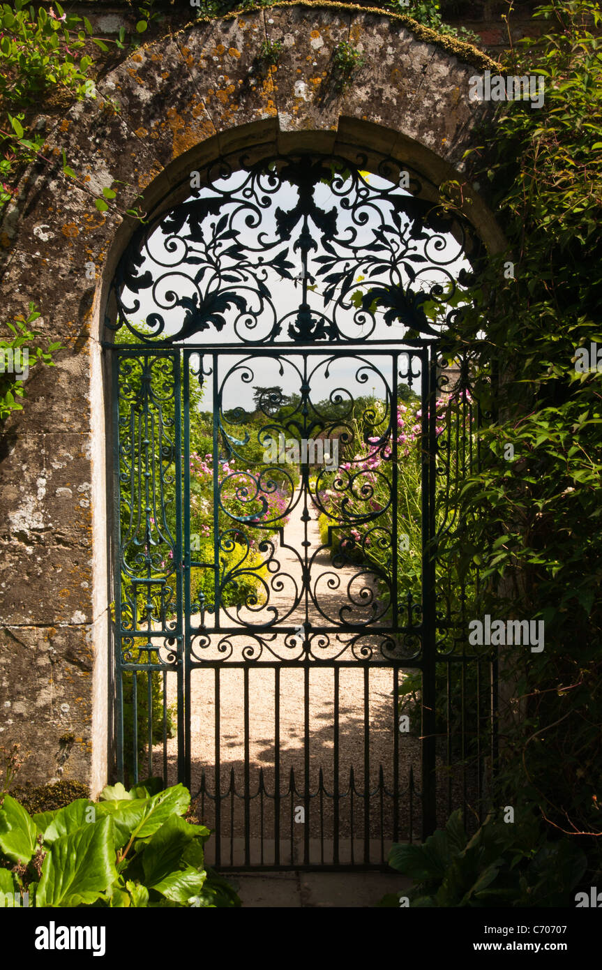 ornate wrought iron gate post ornate wroughtiron gate set in cotswold stone archway leads to the walled garden of rousham house oxfordshire england