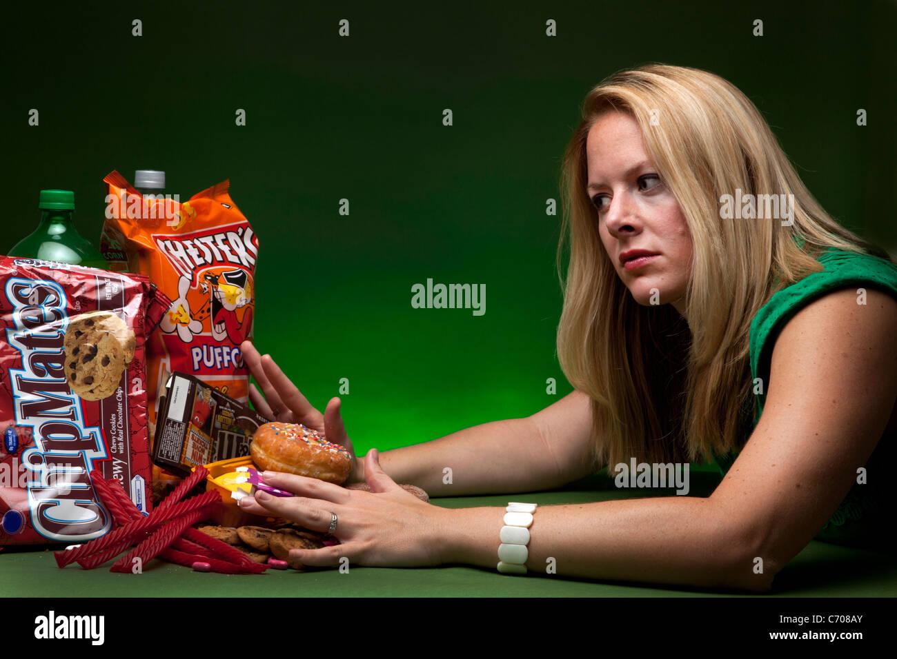 Pushing away junk food, editorial illustration - Stock Image