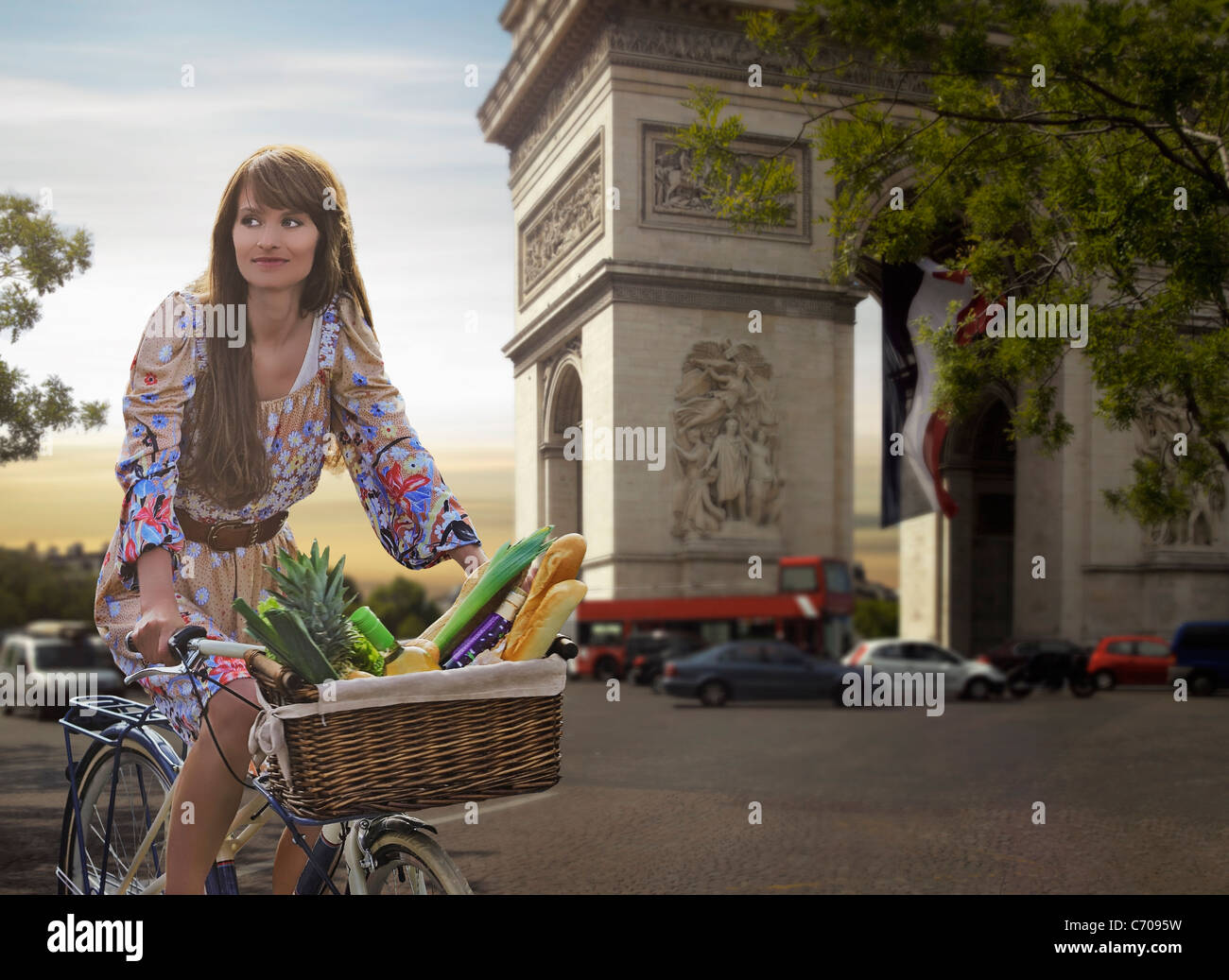 Woman riding bicycle by Arc de Triomphe - Stock Image