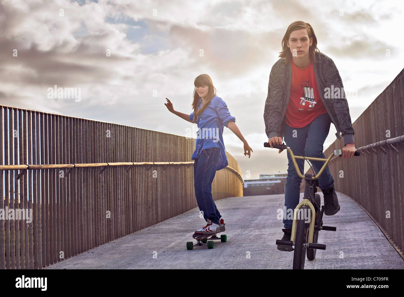 Teenagers riding bicycle and skateboard - Stock Image