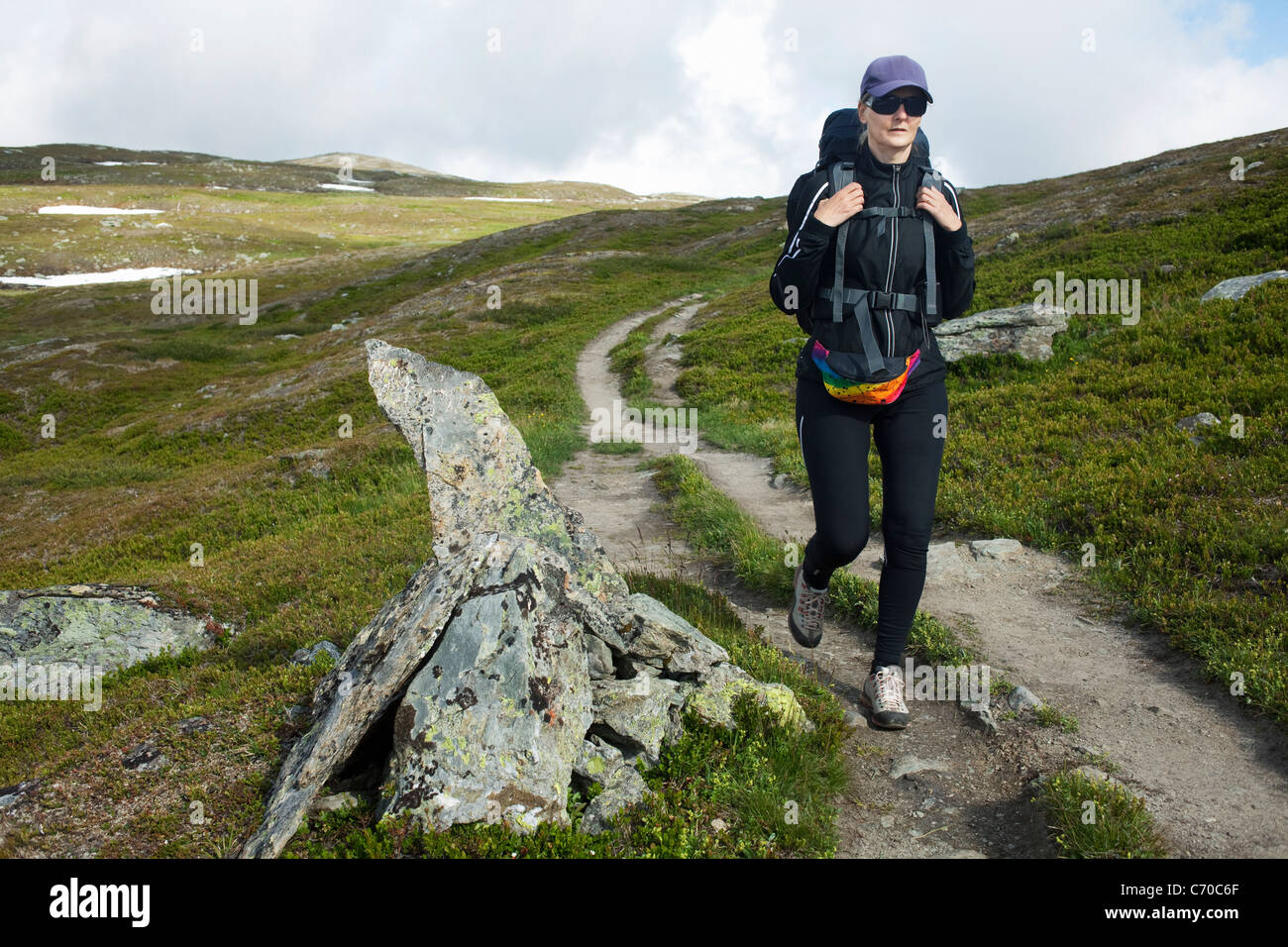 Hiker walking on dirt road - Stock Image
