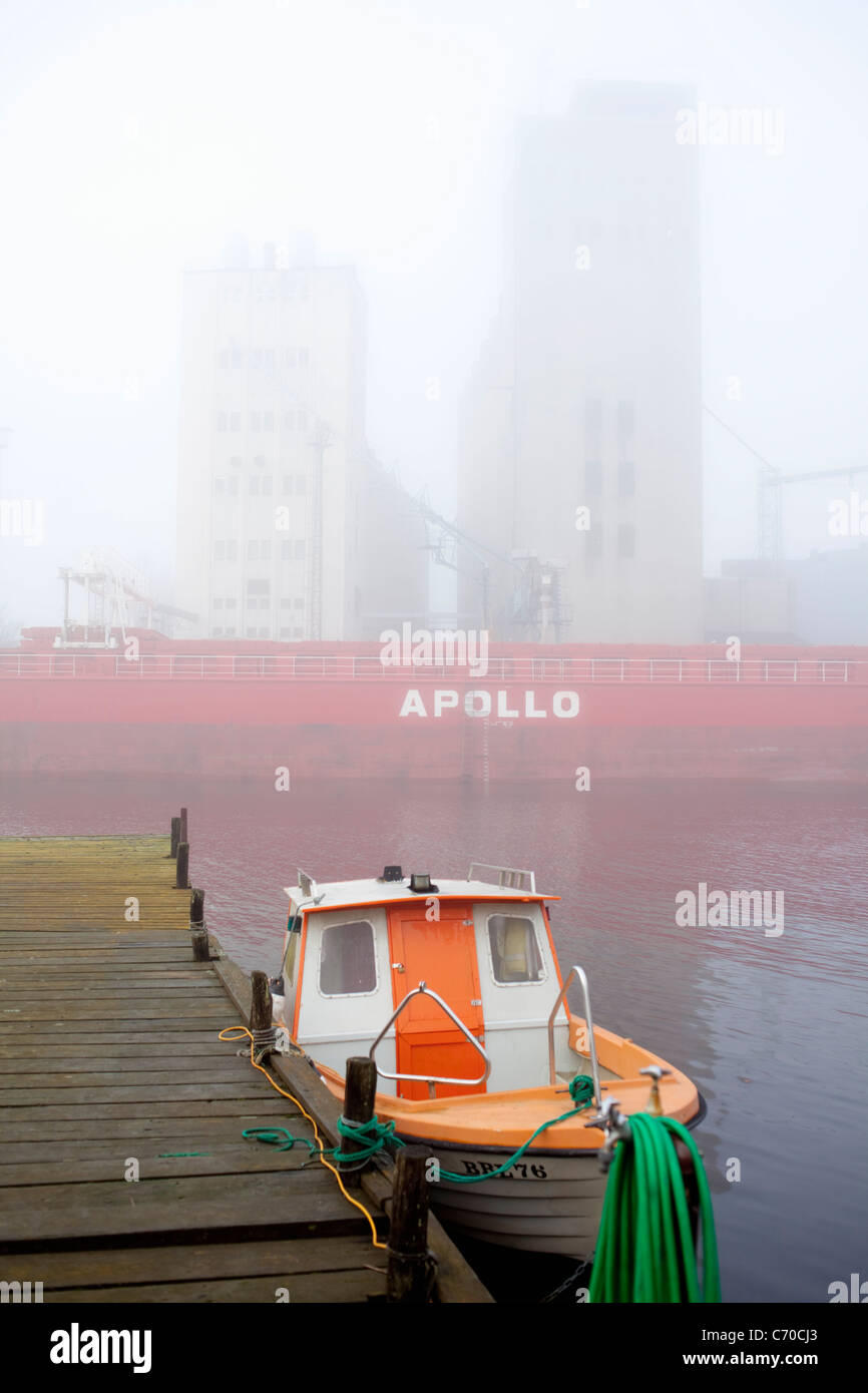 Tugboat docked in urban bay - Stock Image
