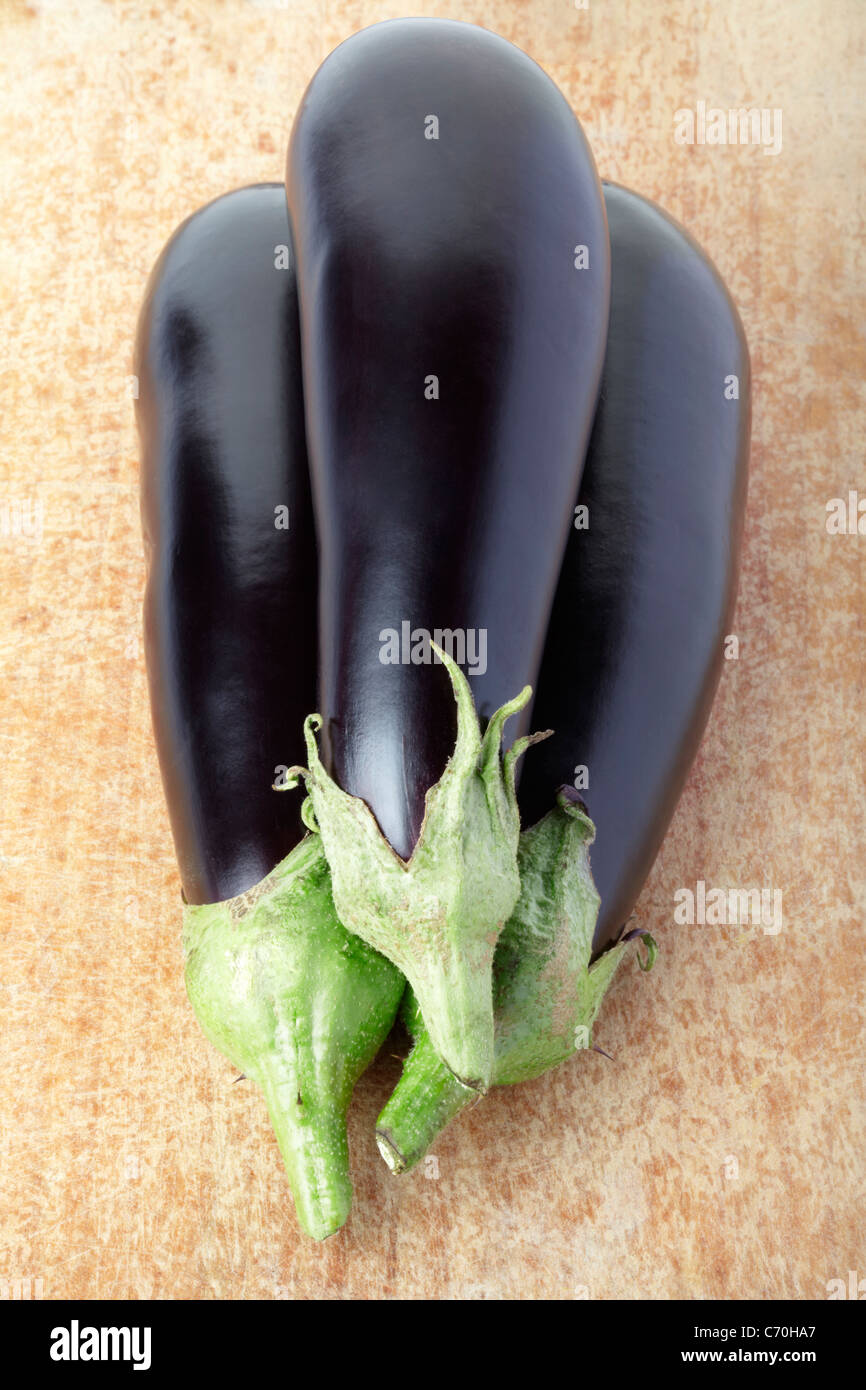 Aubergines on cutting board - Stock Image