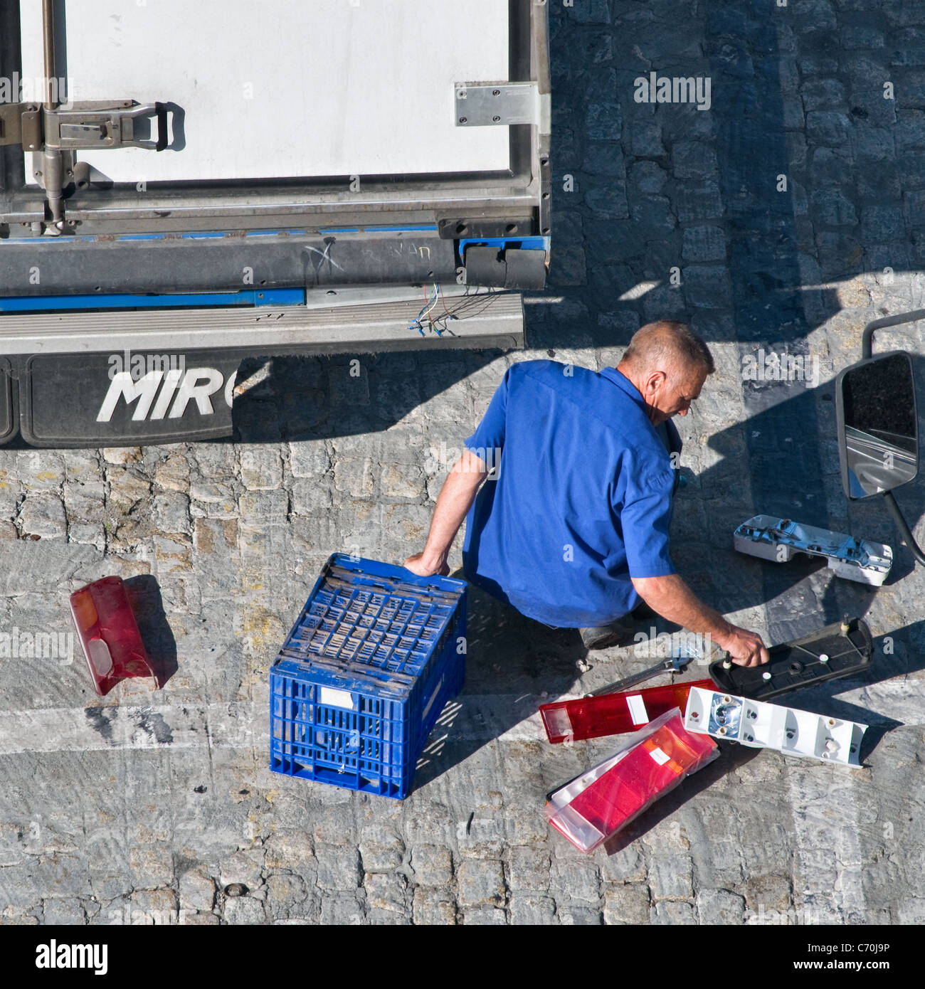 Man replacing the damaged tail lights on a lorry trailer. View from the rear behind. Close up - Stock Image