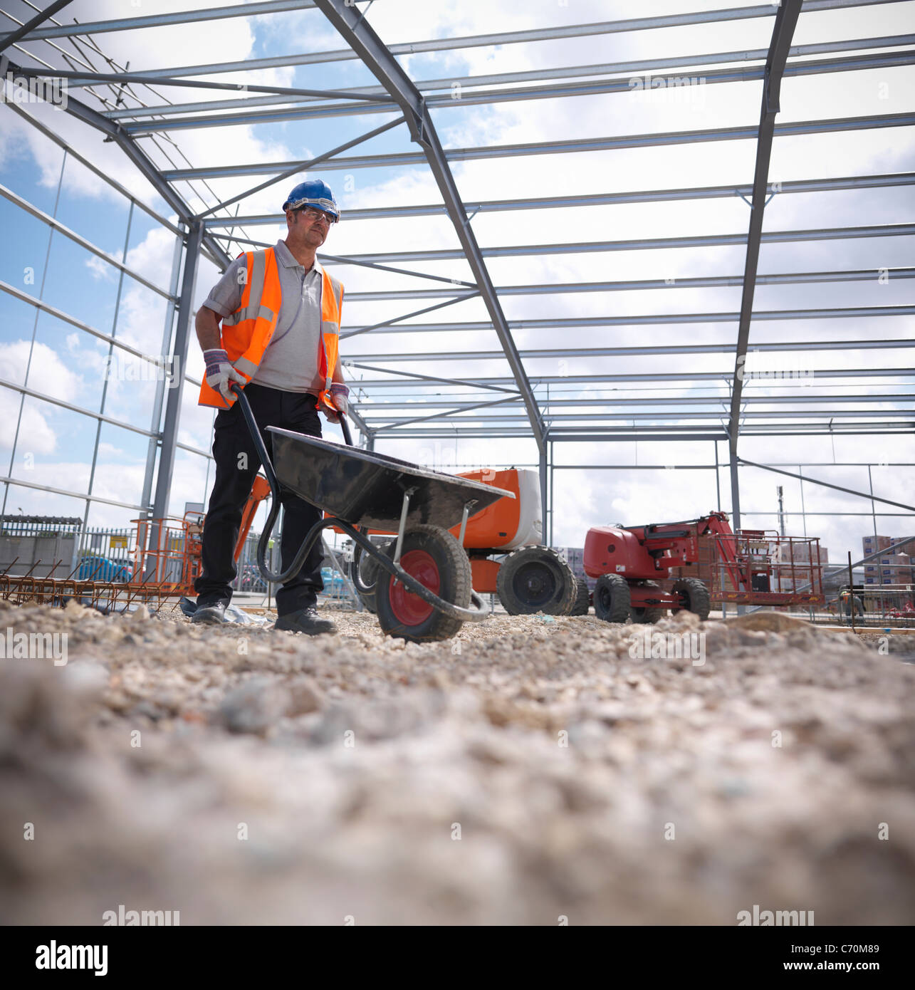 Construction worker with wheelbarrow - Stock Image