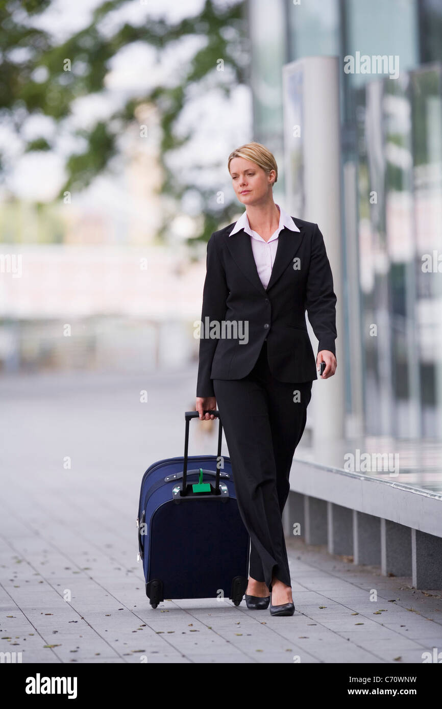 Businesswoman rolling luggage outdoors - Stock Image