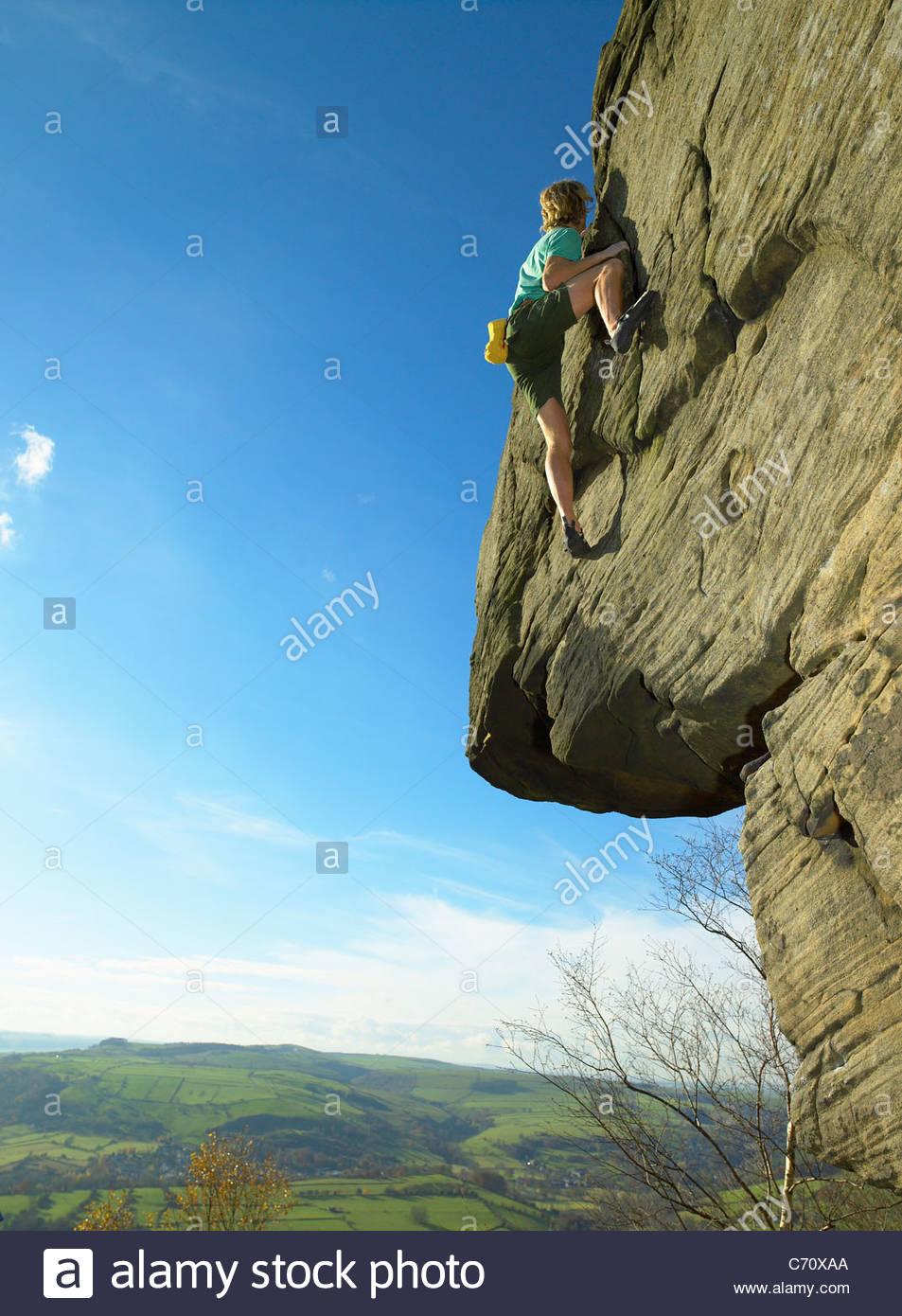 Man climbing rock face - Stock Image
