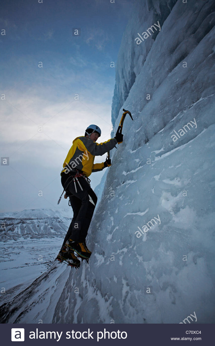 Man climbing glacier with ice pick - Stock Image