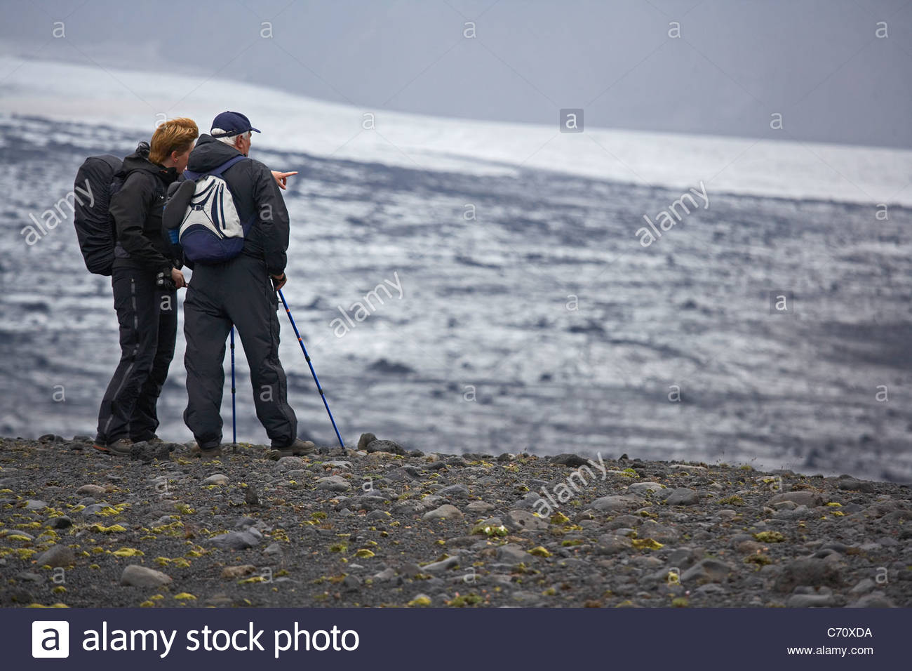 Hikers overlooking snowy landscape - Stock Image
