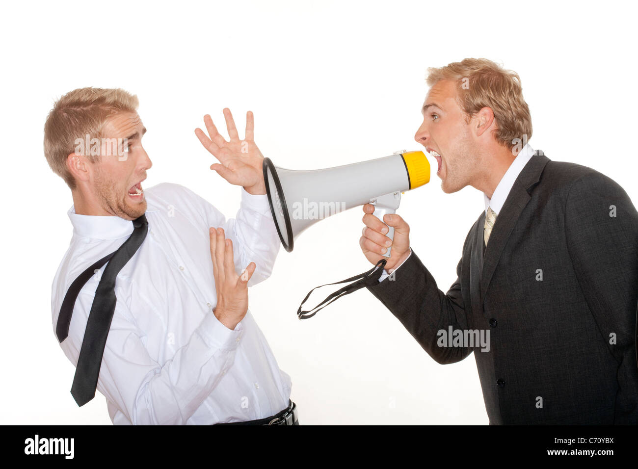 angry boss in suit yelling into a megaphone to scared employee - isolated on white - Stock Image