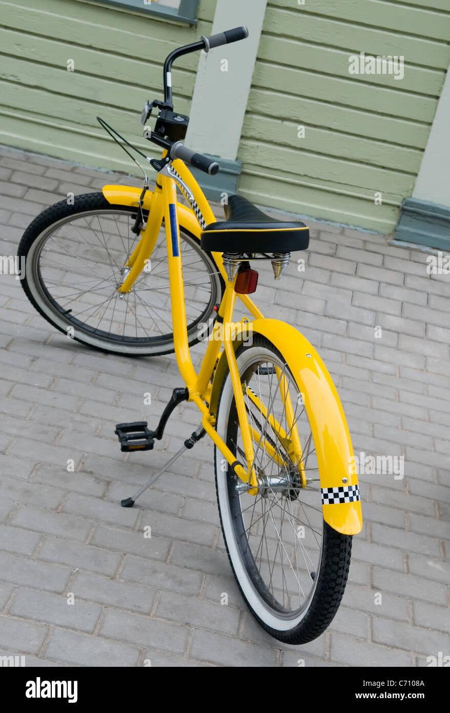 Bicycle of yellow colour with the drawn symbol of a taxi. - Stock Image