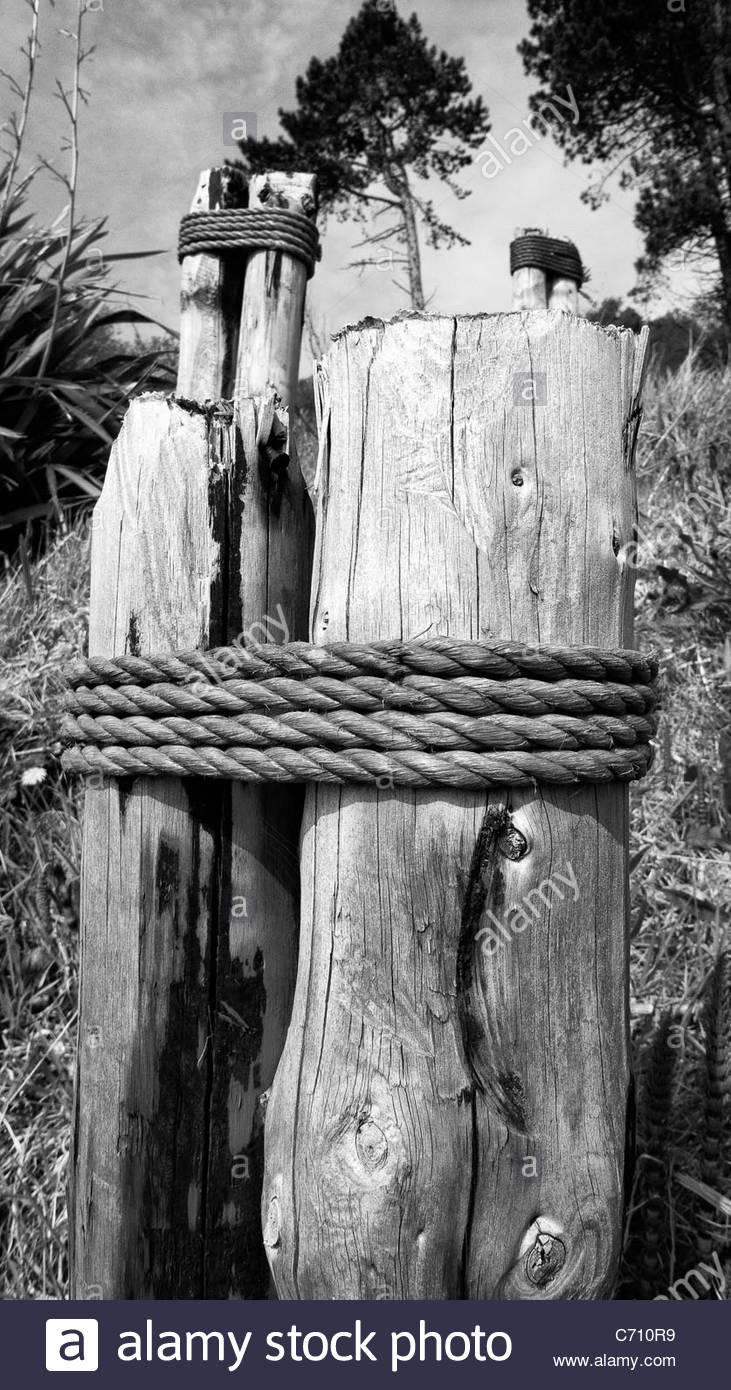Wooden posts and rope by the beach. - Stock Image