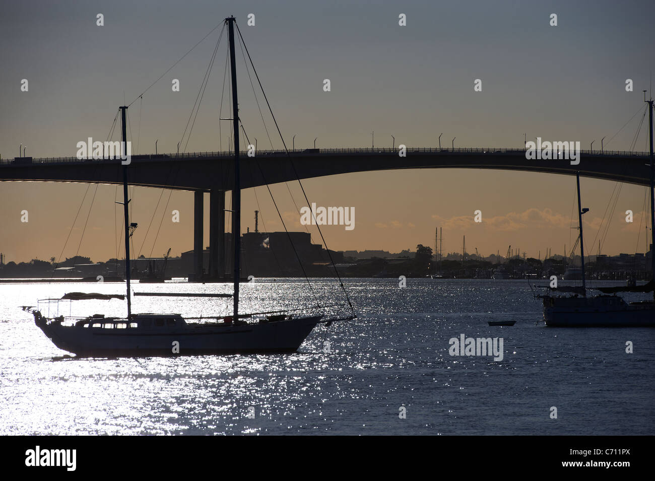 Yacht and Gateway Bridge Brisbane silhouetted by the sunrise - Stock Image
