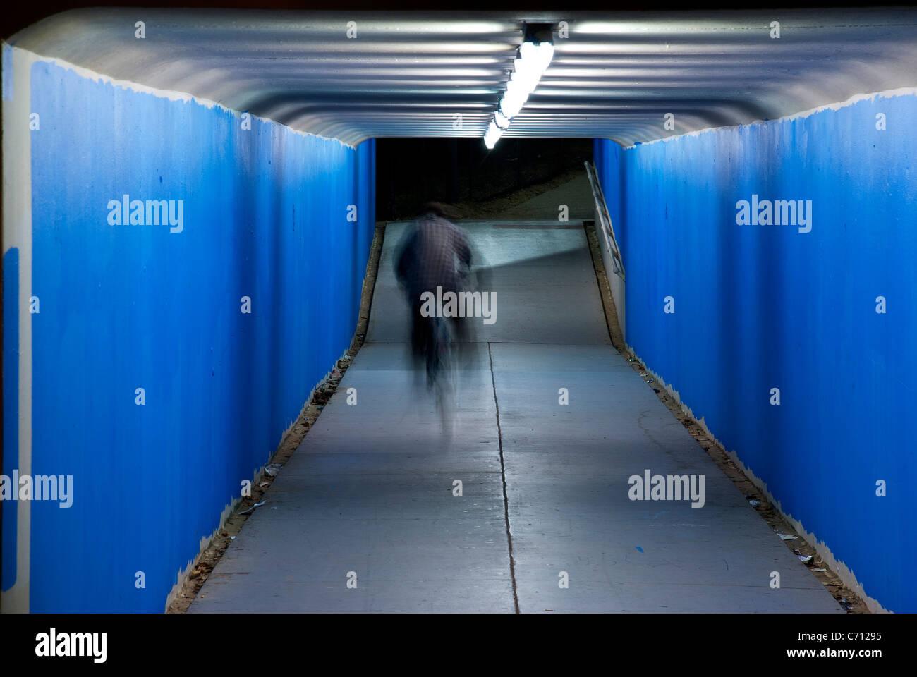 Bike rider in urban tunnel at night - Stock Image