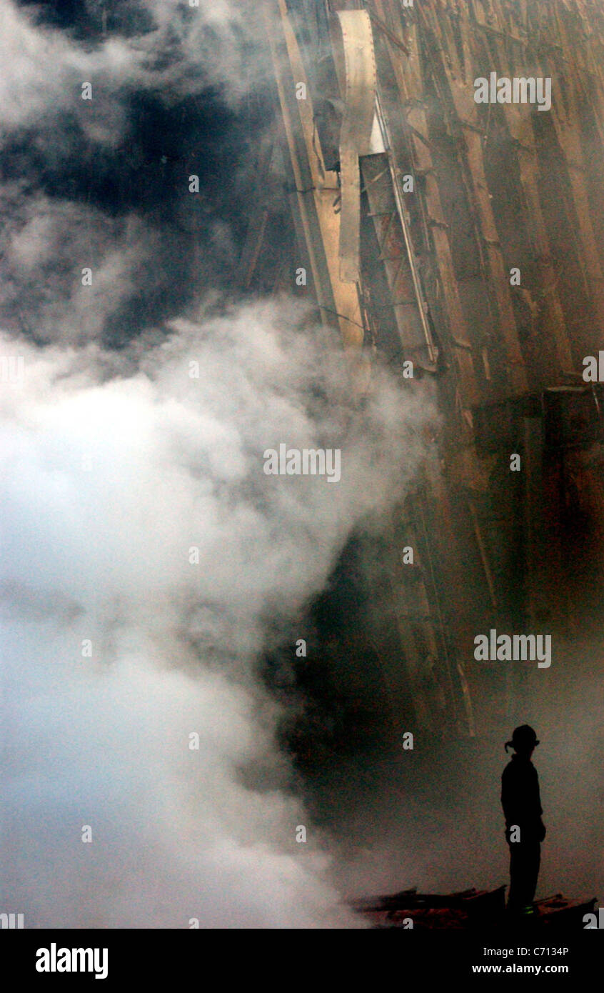 A solitary Firefighter stands watching as smoke rises from the rubble and debris of the World Trade Centers in New - Stock Image