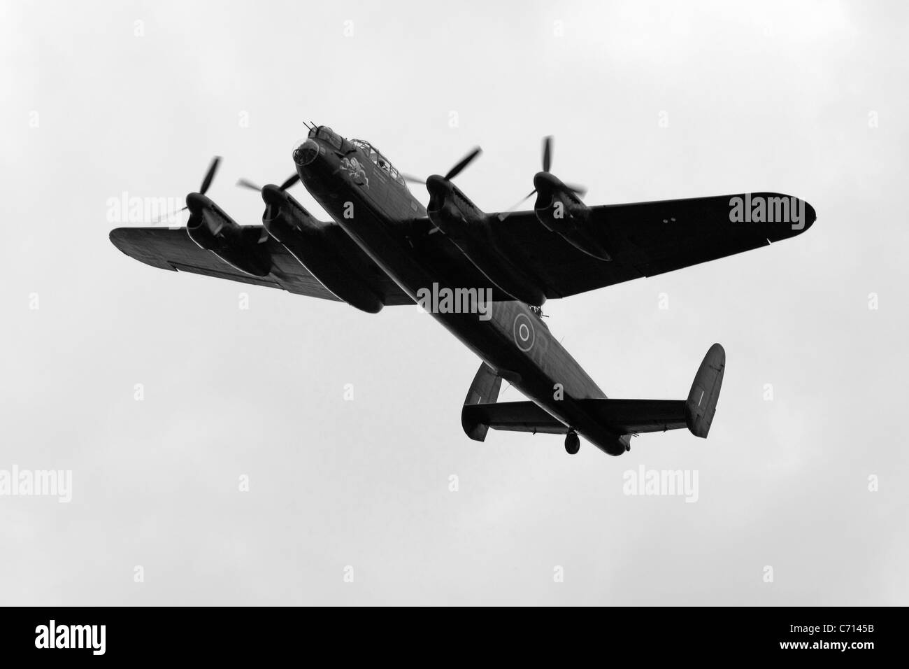 B/W WW2 British RAF Avro Lancaster Bomber Plane on a pass over an airfield during an Airshow - Stock Image