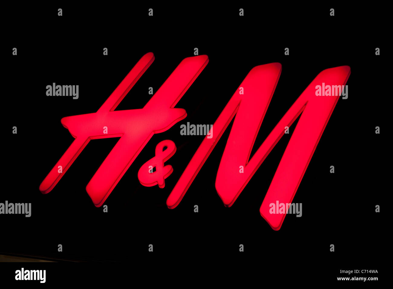 H&M Logo on Shop Front in West End; Oxford Street; illuminated at night; London; England; UK - Stock Image