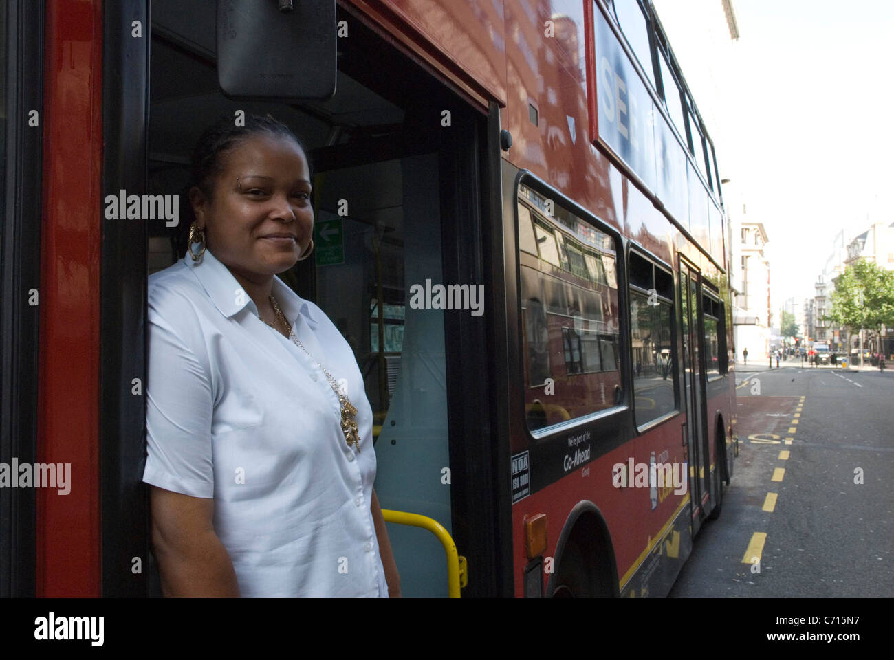 A Woman Bus Driver Stands In Her Traditional London Red