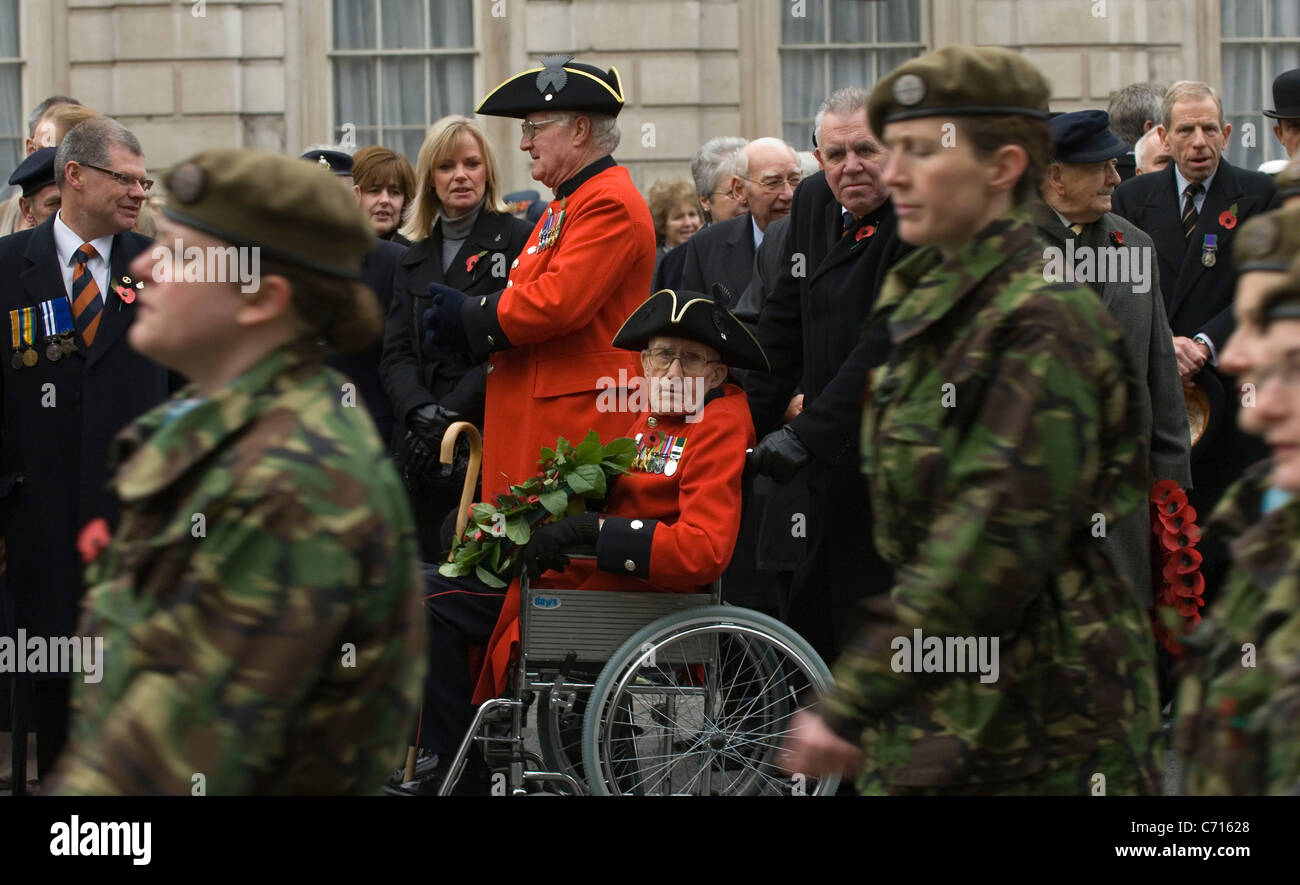 A Chelsea pensioner  pays his respects during remembrance day as soldiers walk past,  London UK - Stock Image