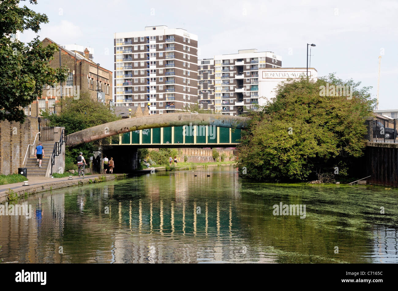 Bridge over the Regent's Canal with people on towpath and flats behind Hackney London England UK - Stock Image
