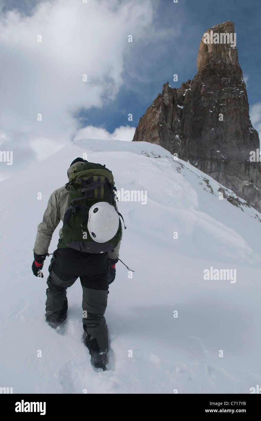 Man hiking along snowy ridgeline below rock spire, Telluride, Colorado. - Stock Image