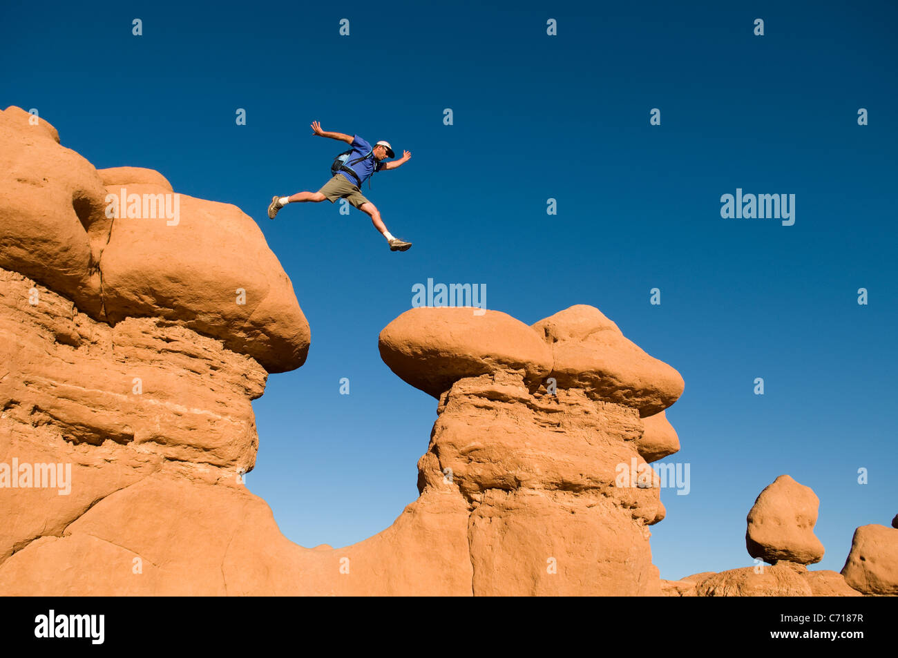 Man jumping between rock spires, Goblin Valley State Park, Hanksville, Utah. - Stock Image