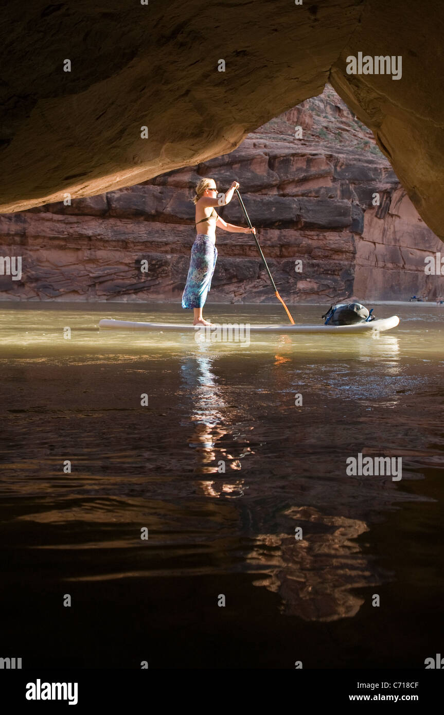 Woman on paddle board in front of cave while rafting down the Lower San Juan River, Mexican Hat, Colorado. - Stock Image