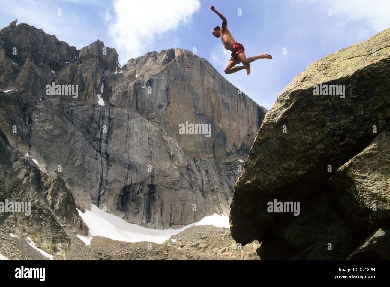 Man jumping off rock below Long's Peak, Rocky Mountain National Park, Estes Park, Colorado. - Stock Image