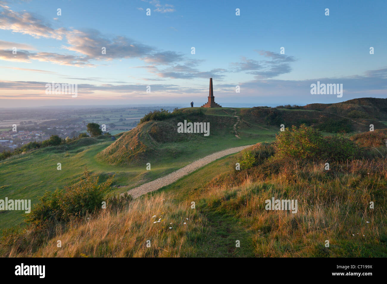 Couple watching sunset from the War Memorial at Ham Hill Country Park. Somerset. England. UK. - Stock Image