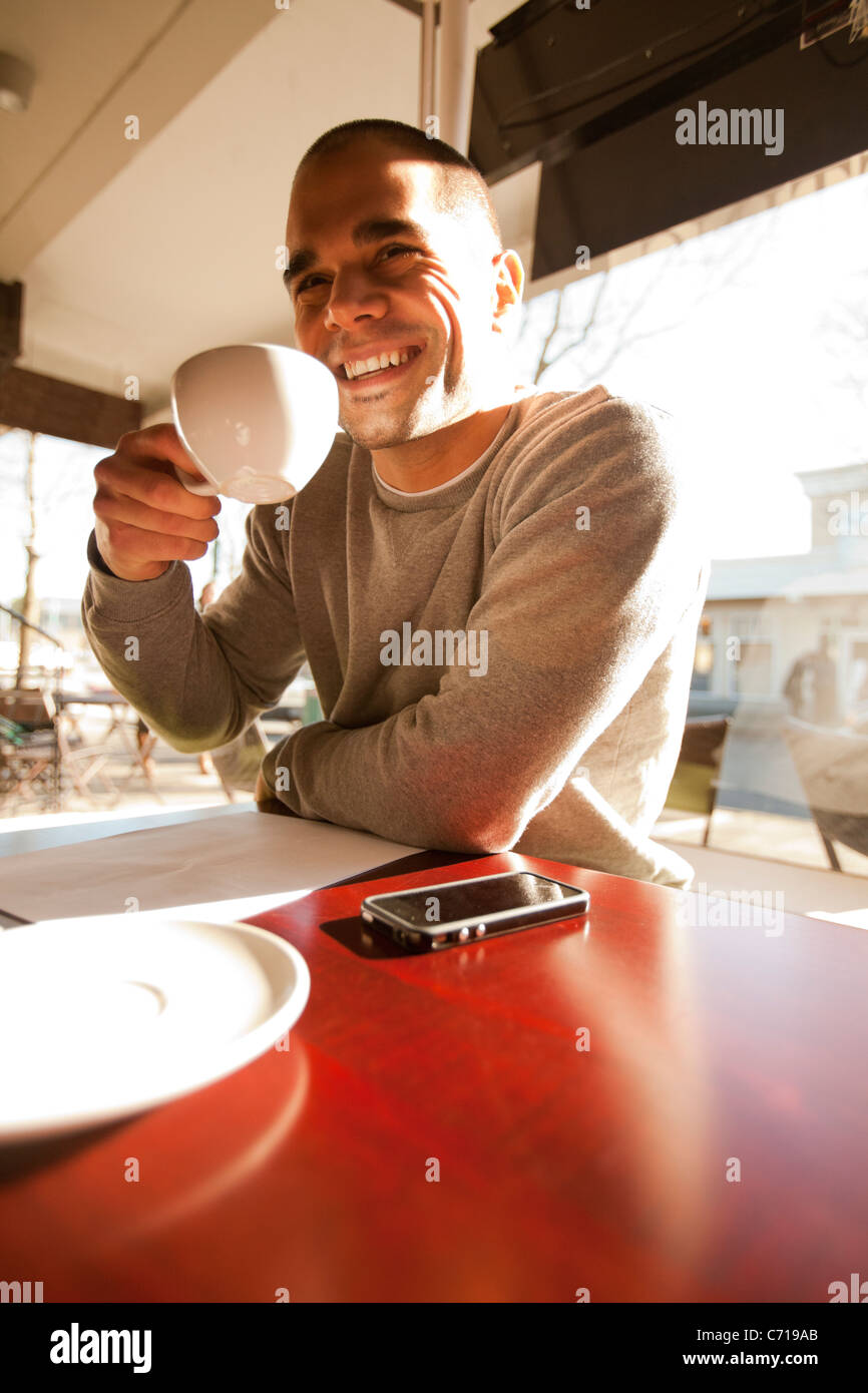 A man enjoying a cup of coffee at a coffee shop. - Stock Image