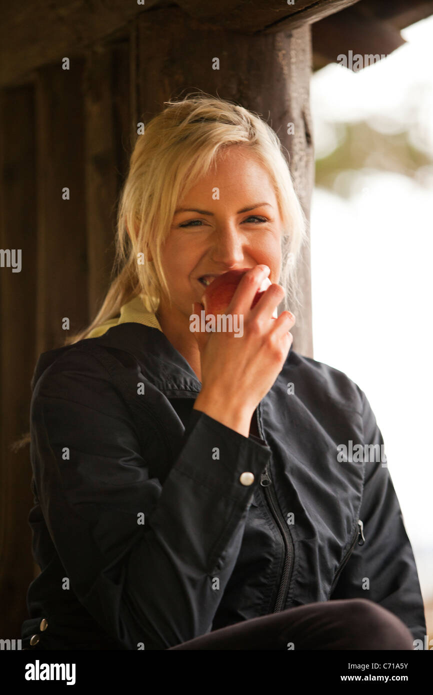 A woman laughs and bites into an apple. - Stock Image